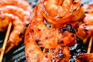 Red spicy shrimp skewers in a grill pan