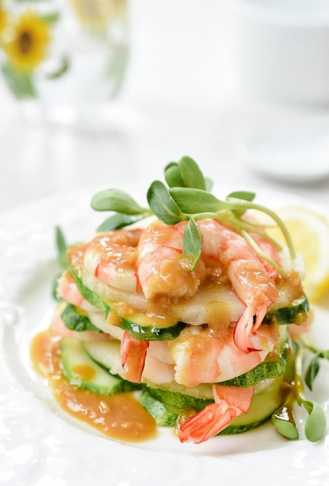 Shrimp salad stacked up on a plate with mustard dressing