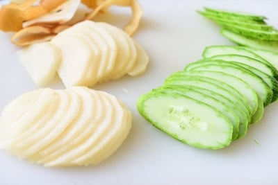 Thinly sliced pear and cucumbers on a cutting board