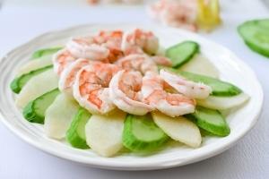 Arranging shrimp salad ingredients on a plate