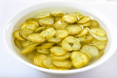 Korean pickled cucumber slices being soaked in water