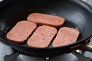 Cooking thin slices of Spam in a pan