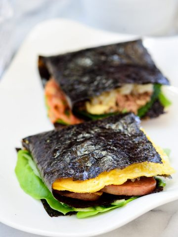 Two folded kimbap on a white plate