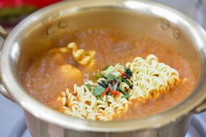 Boiling instant noodles in a spicy broth
