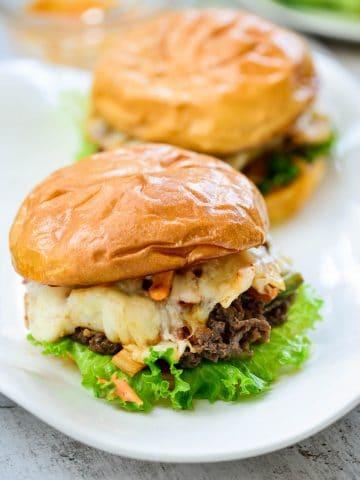 two kimchi bulgogi cheesesteak on hamburger buns with a lettuce leaf