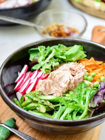 Bibimbap in a large dark color bowl with canned tuna on top with colorful spring vegetables