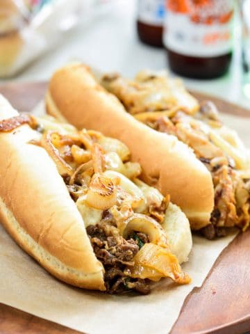 two bulgogi cheese steaks on hoagie buns with beer bottles in the background